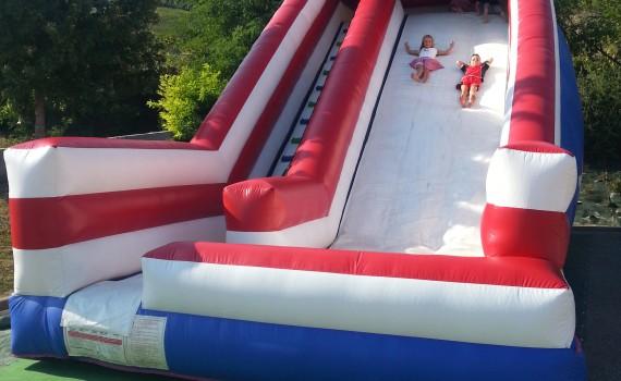 Structure gonflable de jeu en plein air : les enfants glissent dans le toboggan